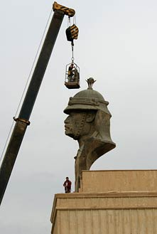 A NEW ERA — Iraqi contractors prepare to remove a statue of Saddam Hussein's head from the Presidential Palace in Baghdad, Iraq, on Dec. 2, 2003. U.S. Air Force photo by Tech. Sgt. John Houghton