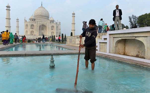 An Indian worker cleans a water pond inside the grounds of the Taj Mahal ahead of US President Barack Obama's visit in Agra Photo: AFP